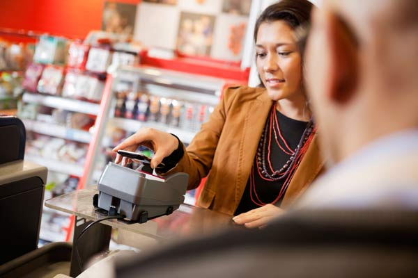 woman making a payment using her phone and NFC