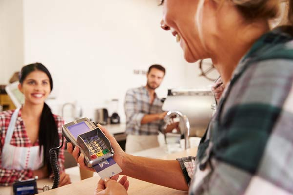 woman paying by credit card in a cafe