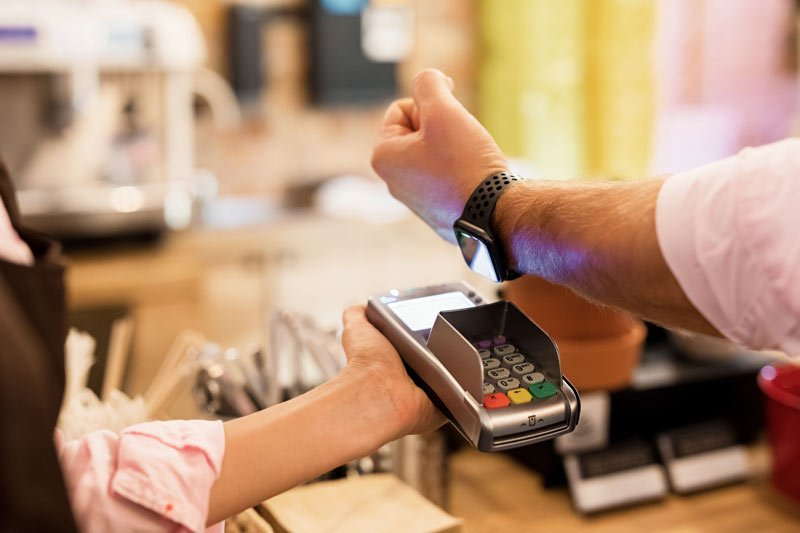 person making a payment using Apple Pay on their smart watch