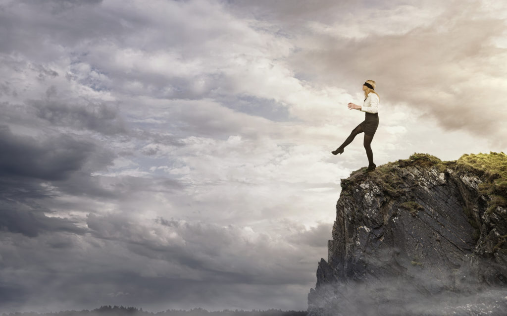 blindfolded business woman stepping off a cliff